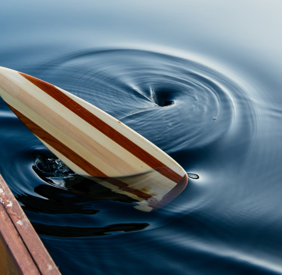 A brown and tan surfboard floats out of a whirlpool of deep blue water