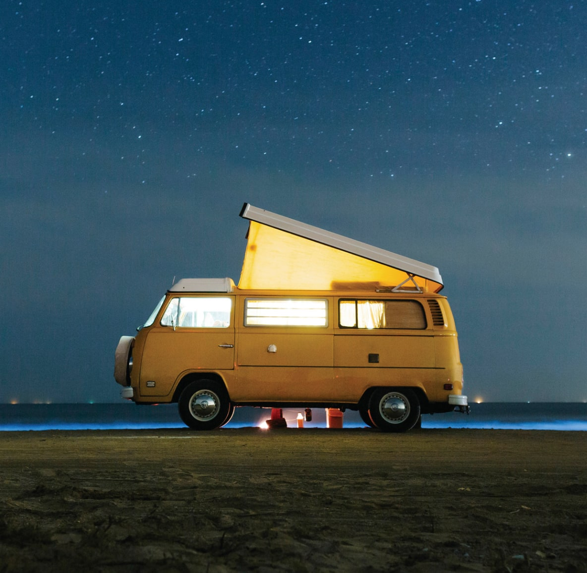 A yellow camper van parked beneath a sky full of stars