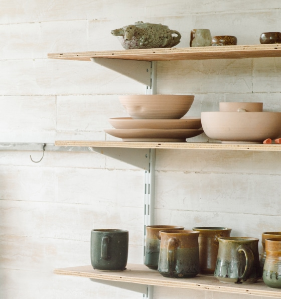 Wooden bowls and ceramic mugs on wooden shelving