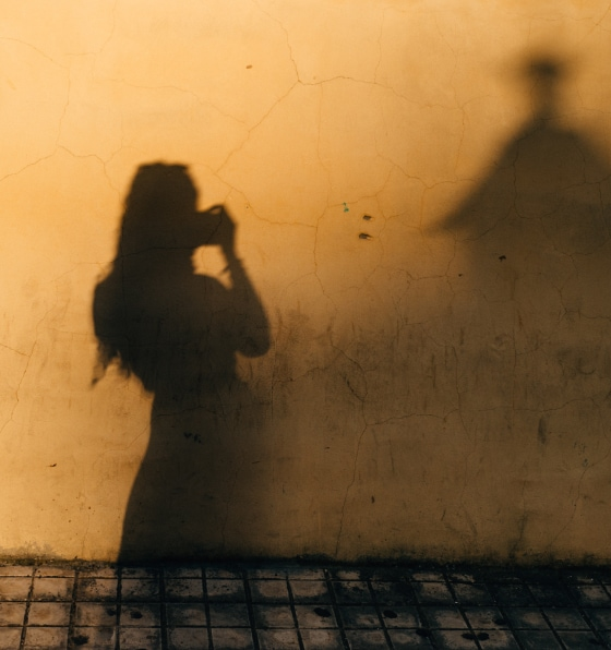 The shadow of a woman taking a picture of herself against a yellow wall