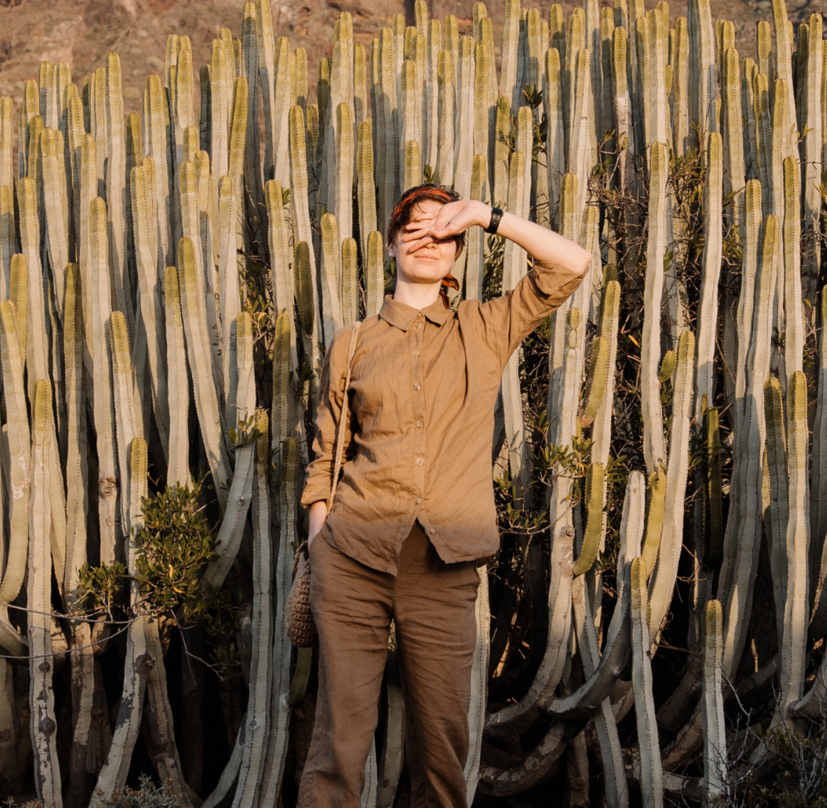 A White woman in a casual beige outfit, shielding her eyes from the sun in front of thin cactus plants