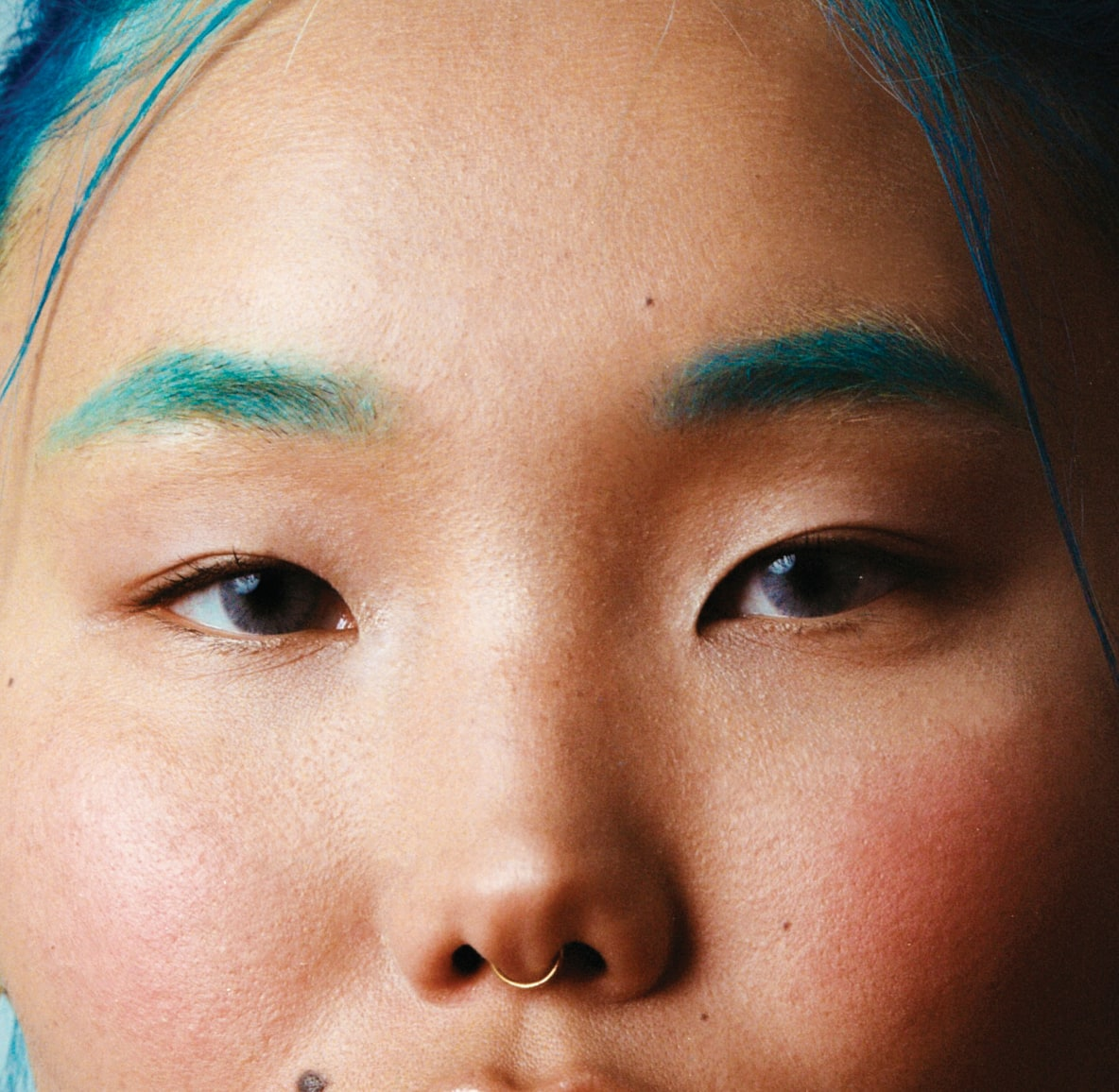 Close-up of a woman with blue hair wearing bright blue eyeshadow on her eyebrows