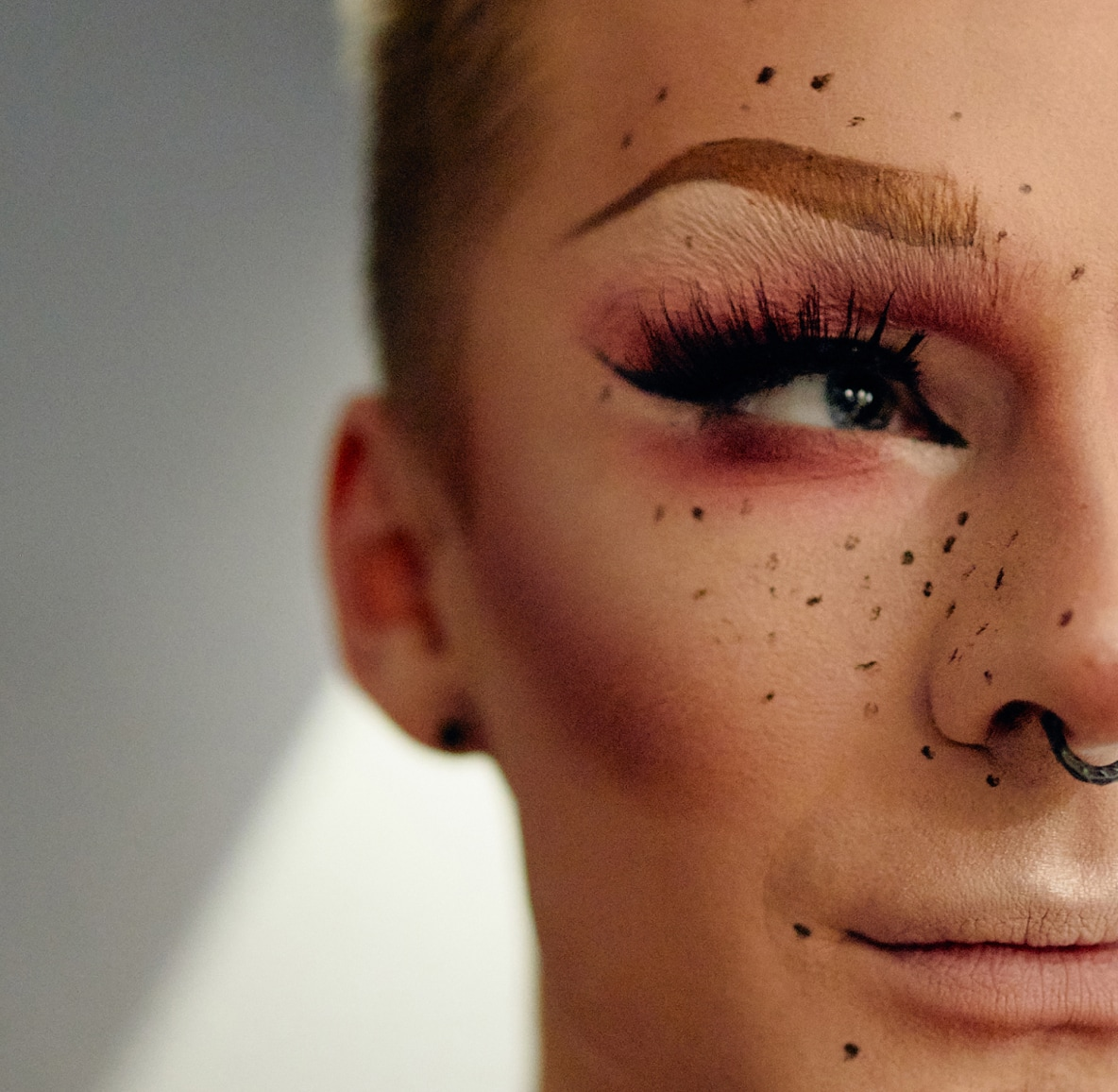 Closeup of drag queen with dramatic makeup of freckles, eyebrows and pink eyeshadow