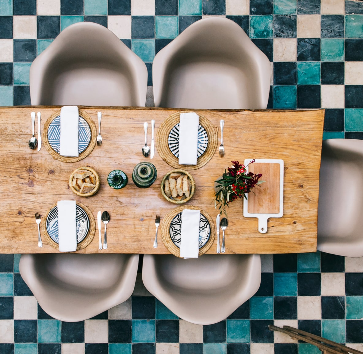 Overhead view of elegant tablescape featuring food and cutlery amidst a checkered flooring pattern