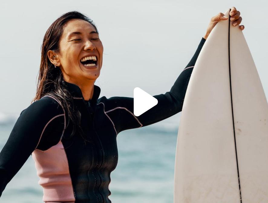 Femme d'Asie de l'Est riant et tenant sa planche de surf à la plage