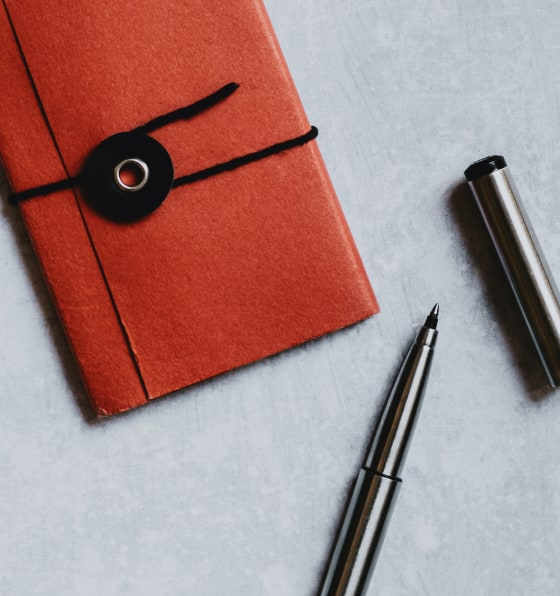 Mini red notebook sitting next to an open black pen