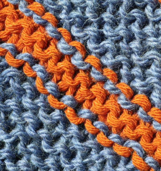 Closeup shot of blue knitted material with orange stripes down the middle