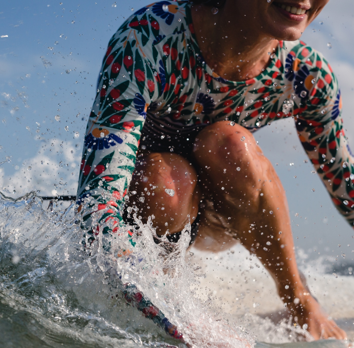 A smiling woman in a floral swim top ride a surfboard