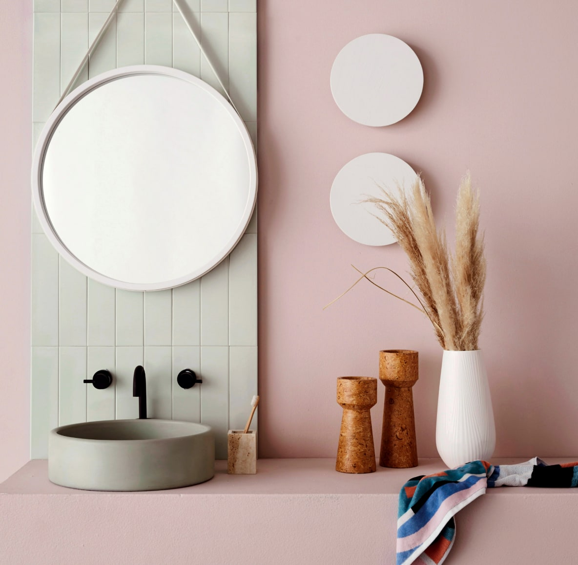 Modern bathroom sink with a mirror and ceramic vase