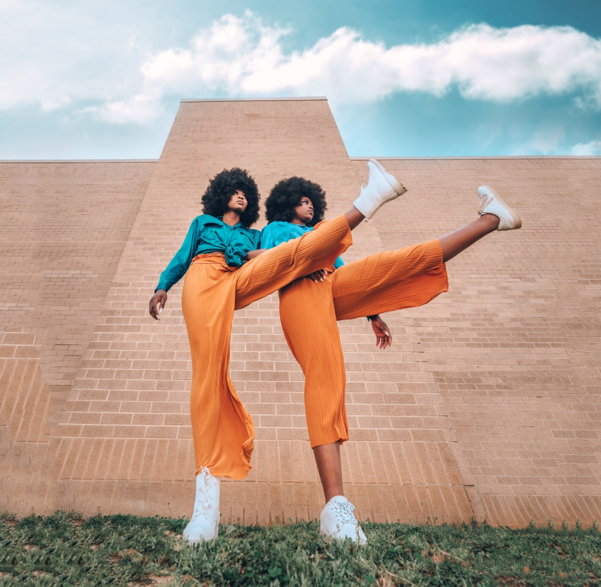 Two women kicking their legs up wearing matching long-sleeved tops in teal and flowing trousers in orange
