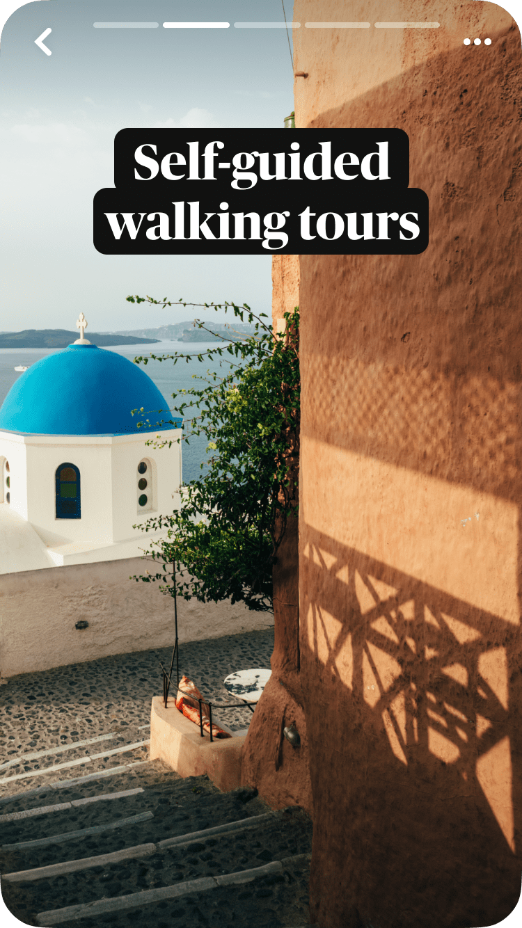 Stone steps leading to the blue domed church in Santorini, Greece, framed against the sea in the background, with a text overlay, Self-guide walking tours