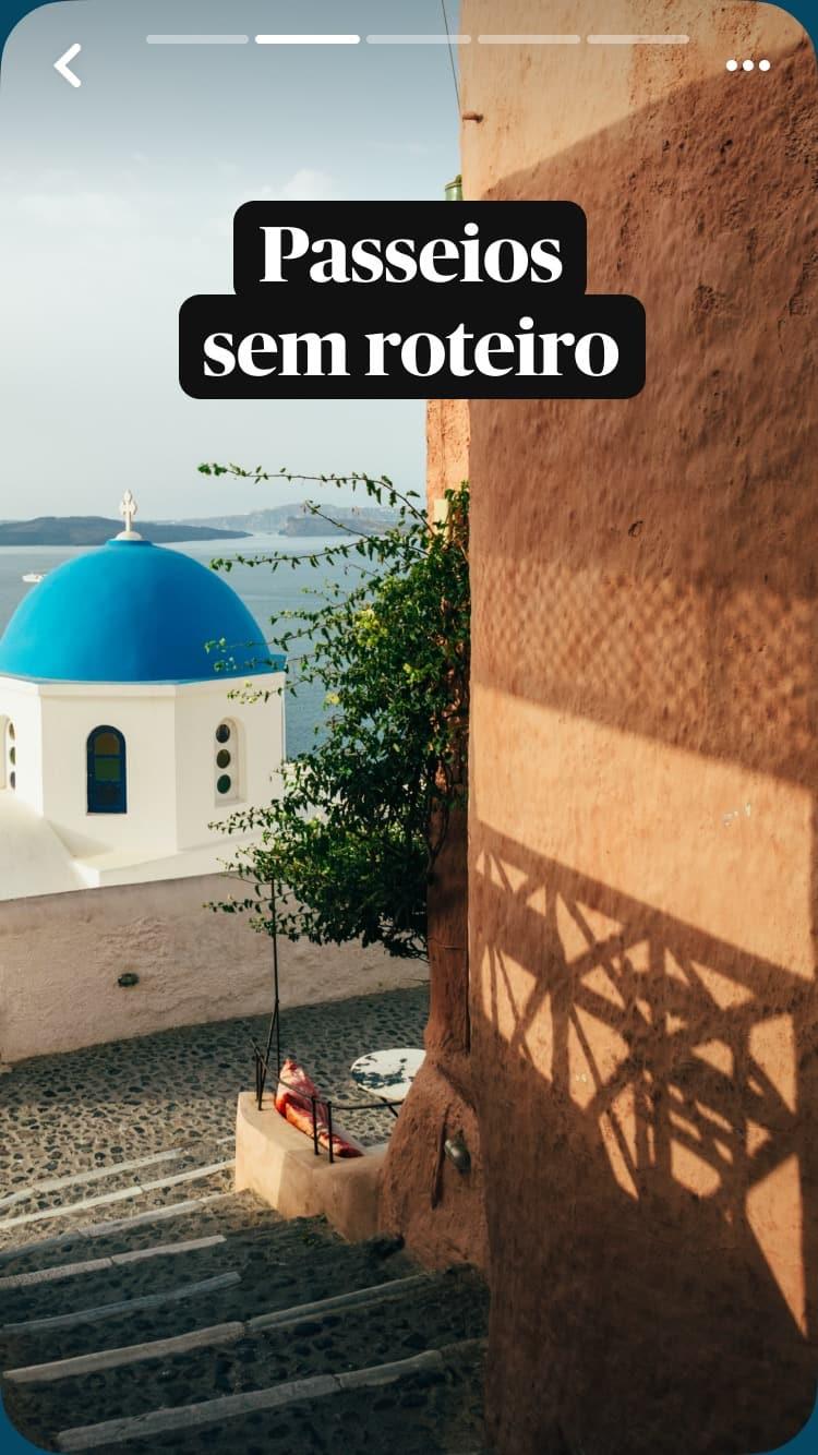 Degraus de pedra levando até a igreja de cúpula azul em Santorini, na Grécia, com o mar ao fundo e uma sobreposição de texto: Passeios sem roteiro