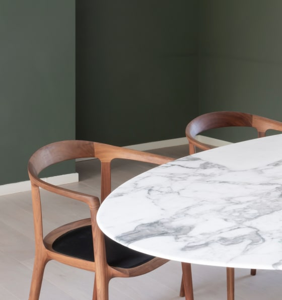 Marble table with two wooden chairs in front of a deep green wall