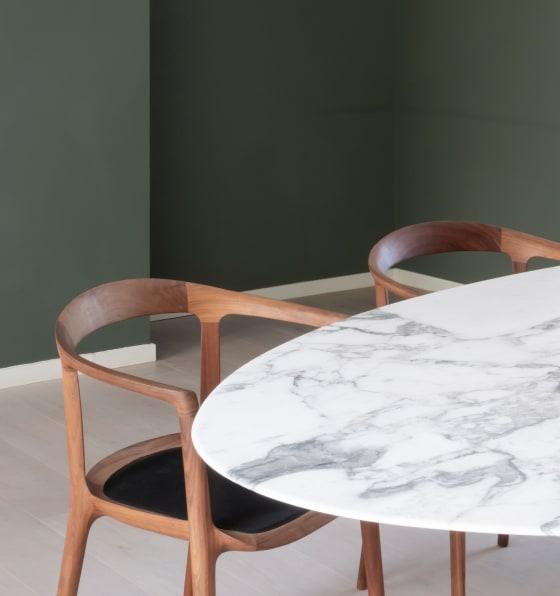 Marmortisch mit zwei Holzstühlen vor einer tiefgrünen Wand