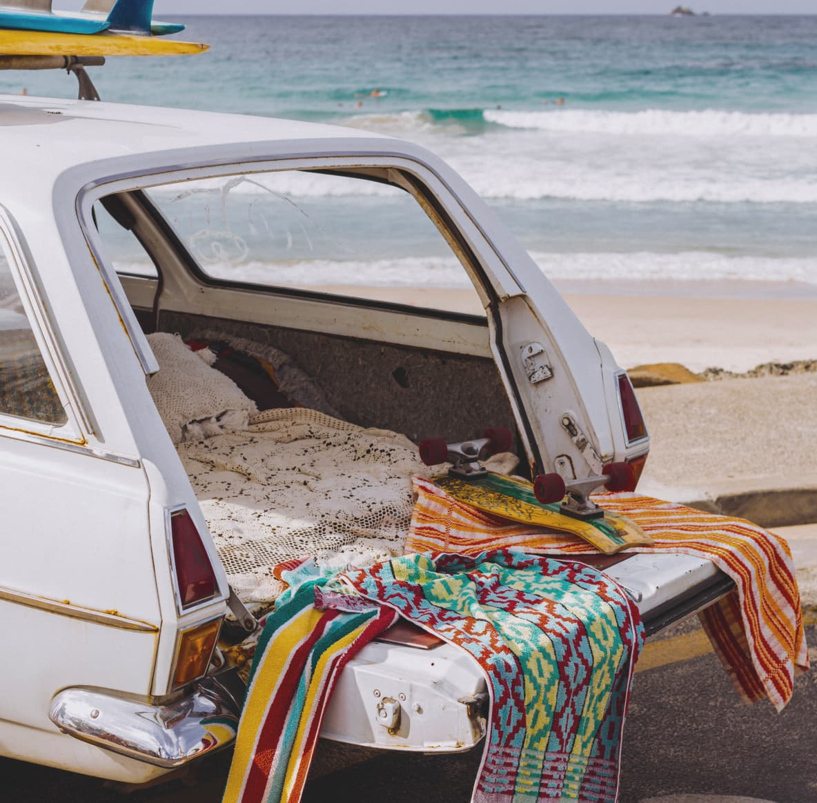 The open back of a white station wagon covered in beach towels, surf boards on top and the ocean in the background