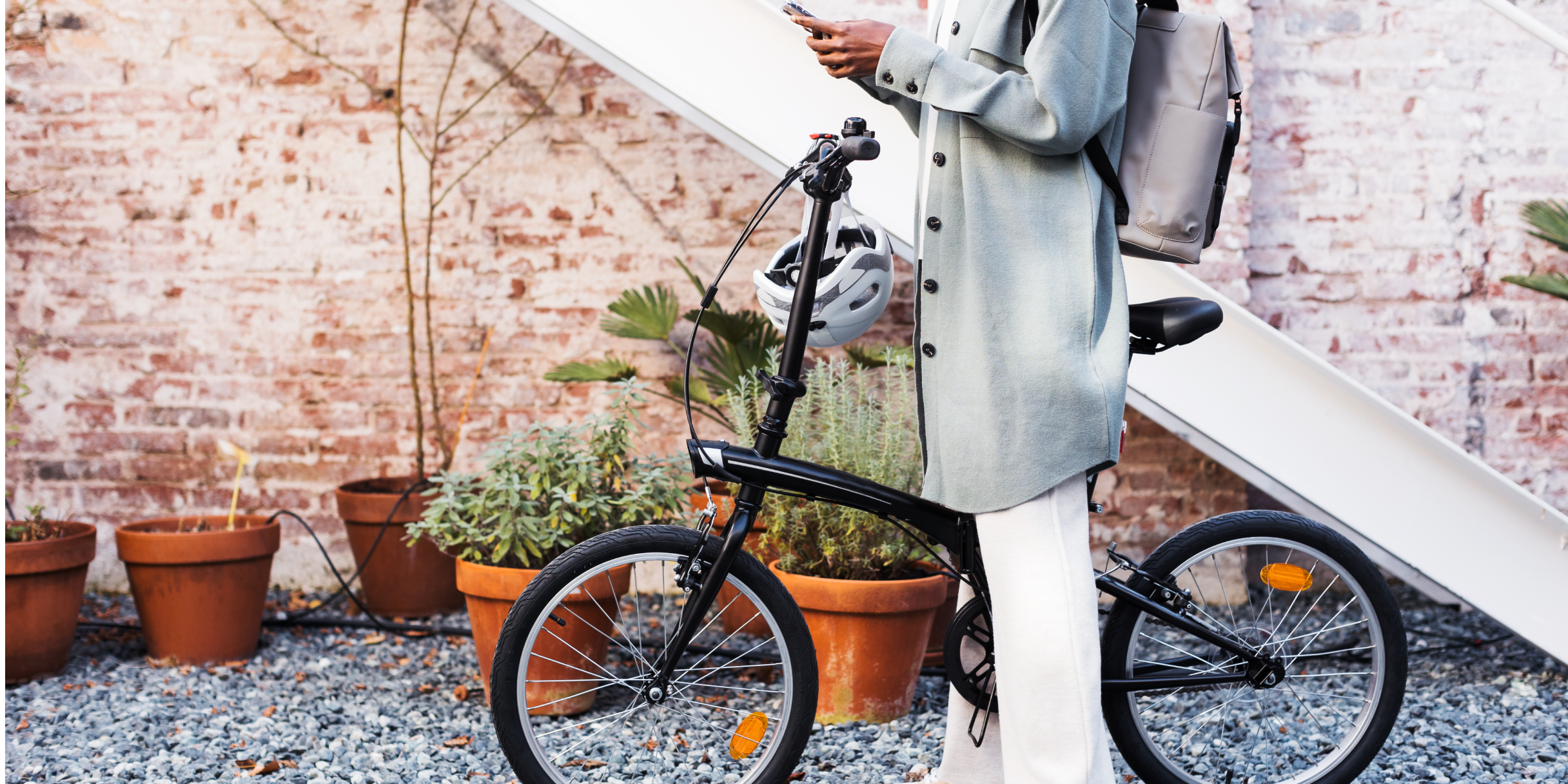 A person in a gray coat stands near a brick wall and straddles a black bicycle