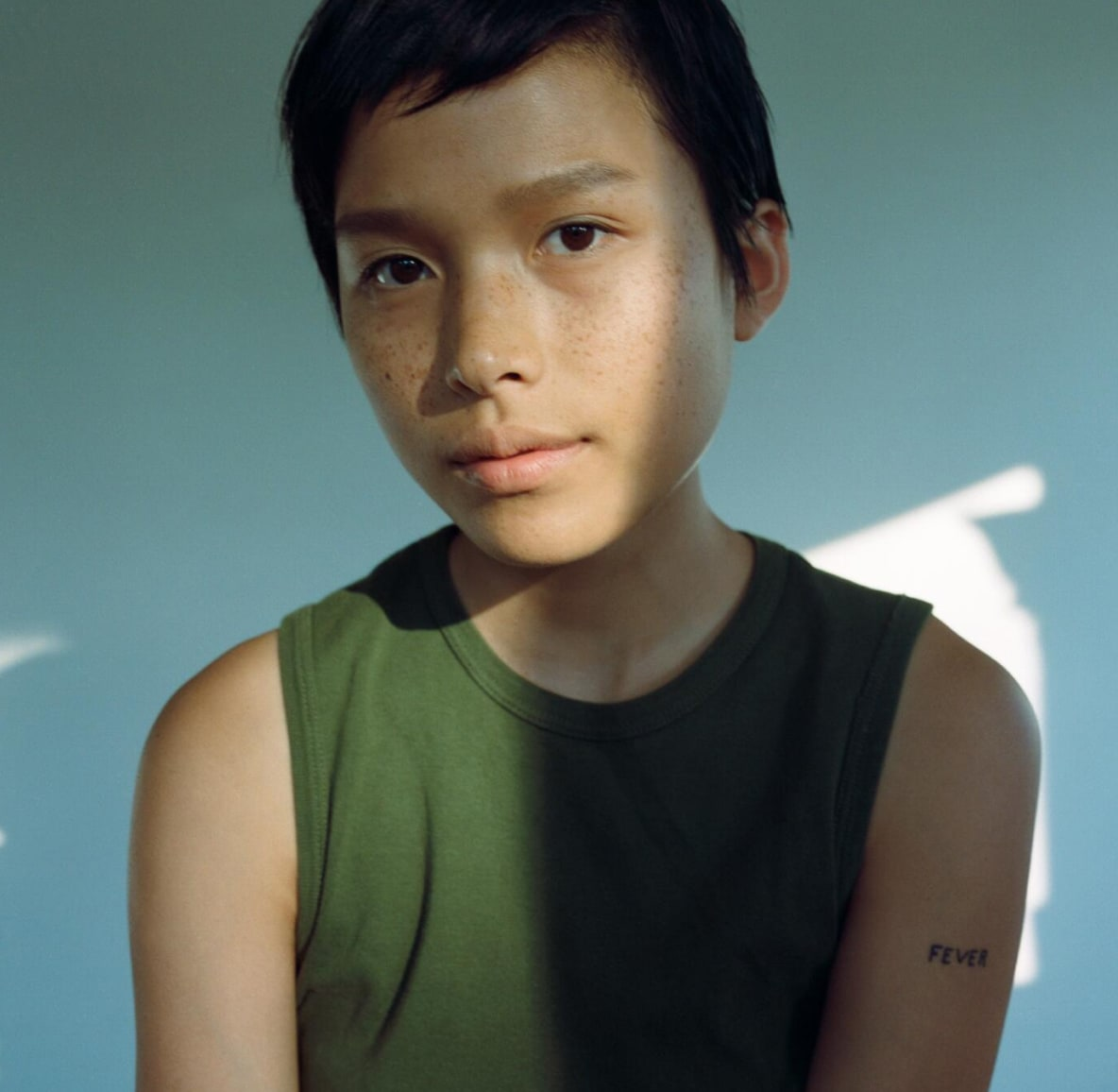 Young person with short black hair, a green tank top and no makeup