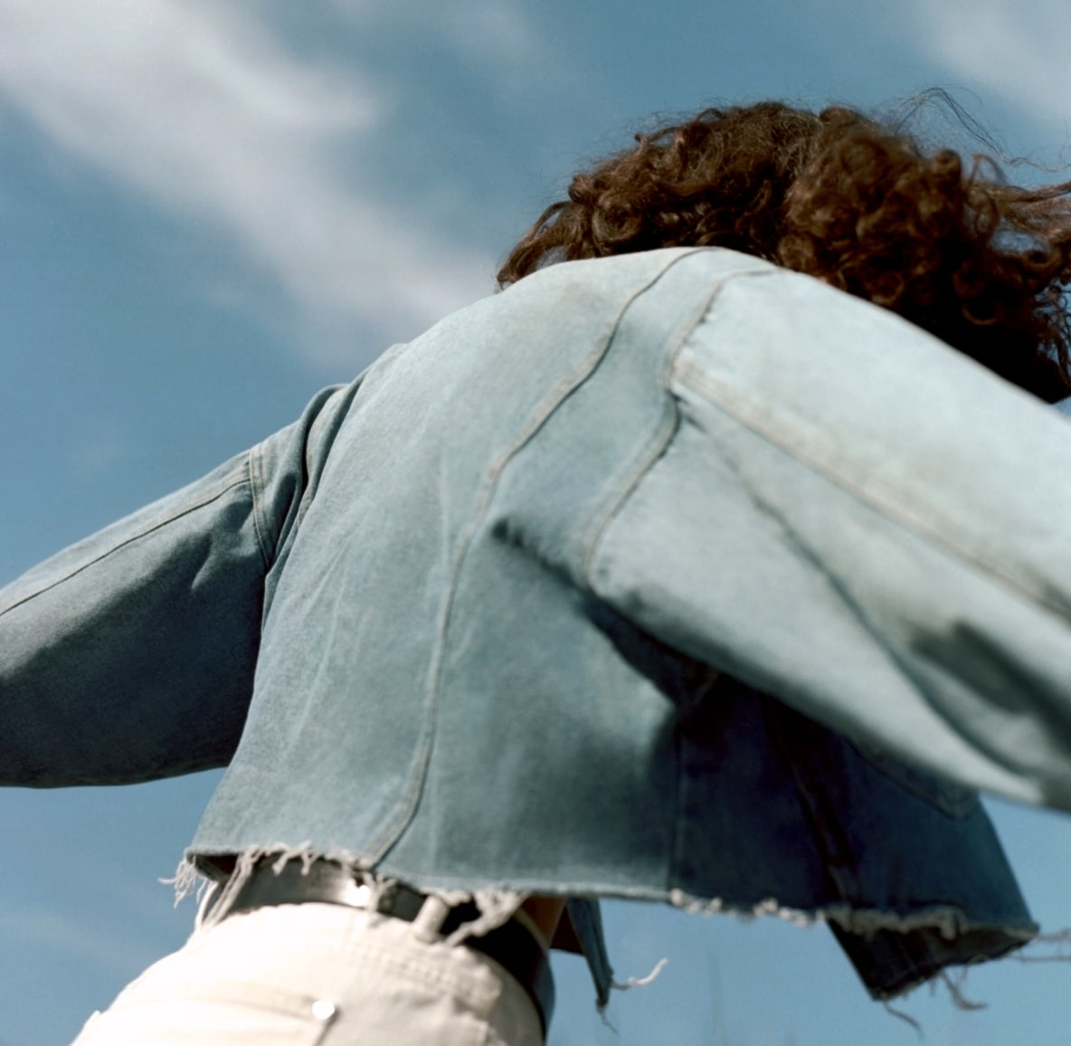 Woman with curly hair facing away from the camera wearing denim jacket and white pants