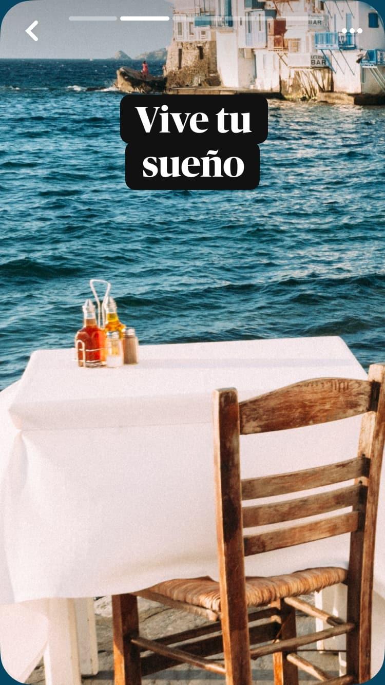 """Una mesa dispuesta para uno en un café al aire libre, cubierta con un mantel blanco; en el fondo, se ven el mar y edificios, y el texto superpuesto es """"Vive tu sueño"""""""