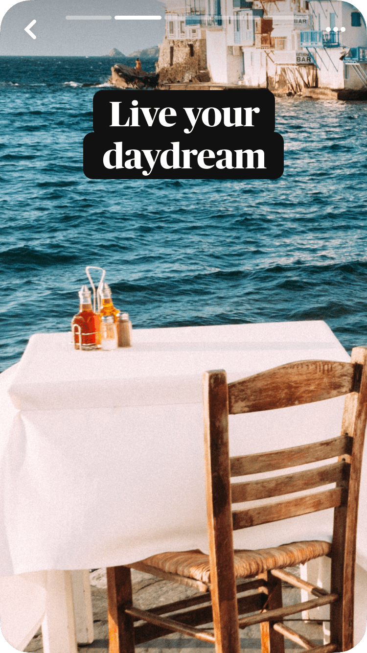 A single table setting at an outdoor cafe covered with a white tablecloth, the sea and buildings in the background, with a text overlay, Live your daydream