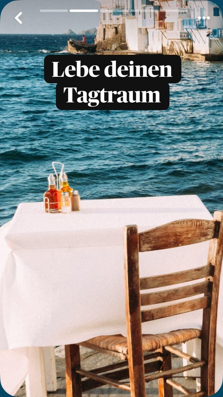 Ein einzelner gedeckter Tisch eines Cafés im Freien mit weißer Tischdecke. Im Hintergrund das Meer und Gebäude. Auch im Bild ist ein Text-Overlay: Lebe deinen Tagtraum.