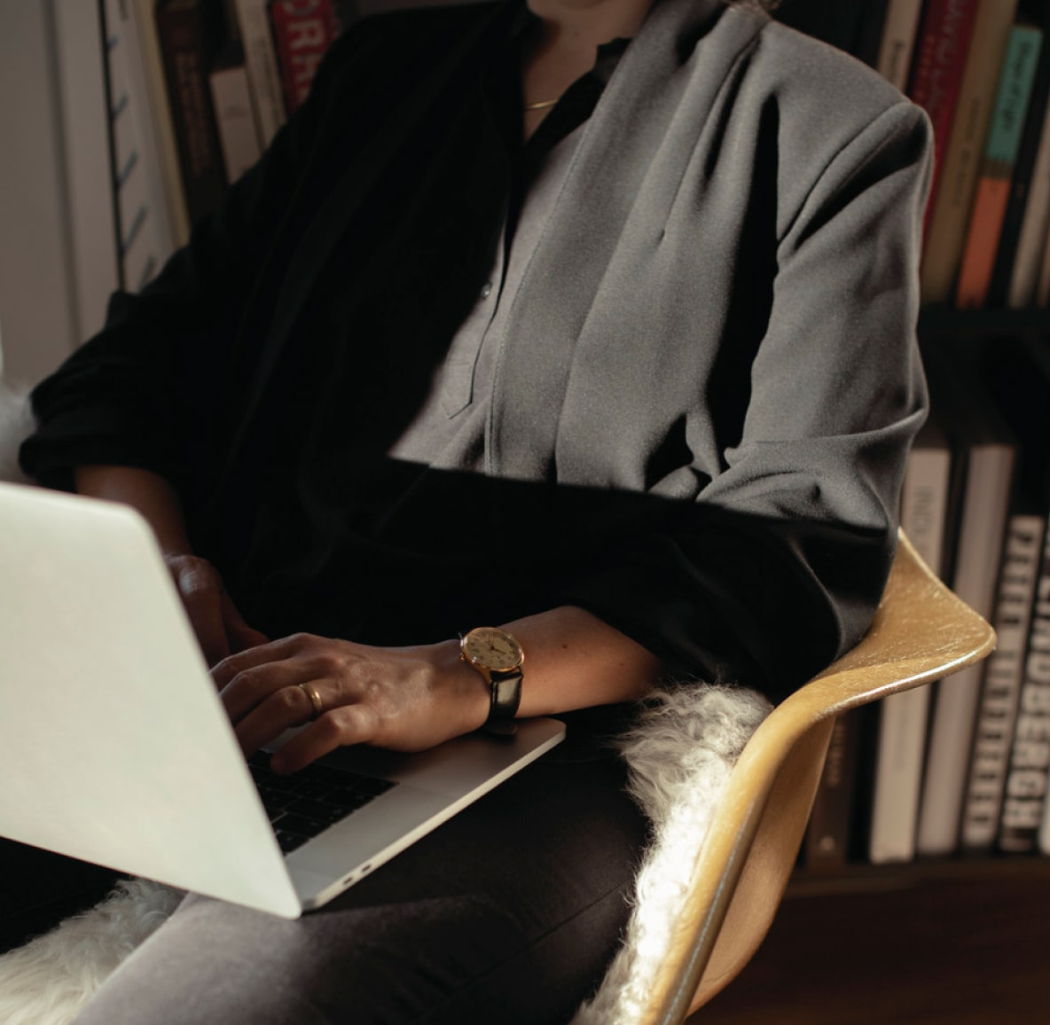 Woman in flowy black blazer sitting in a chair and typing on her laptop