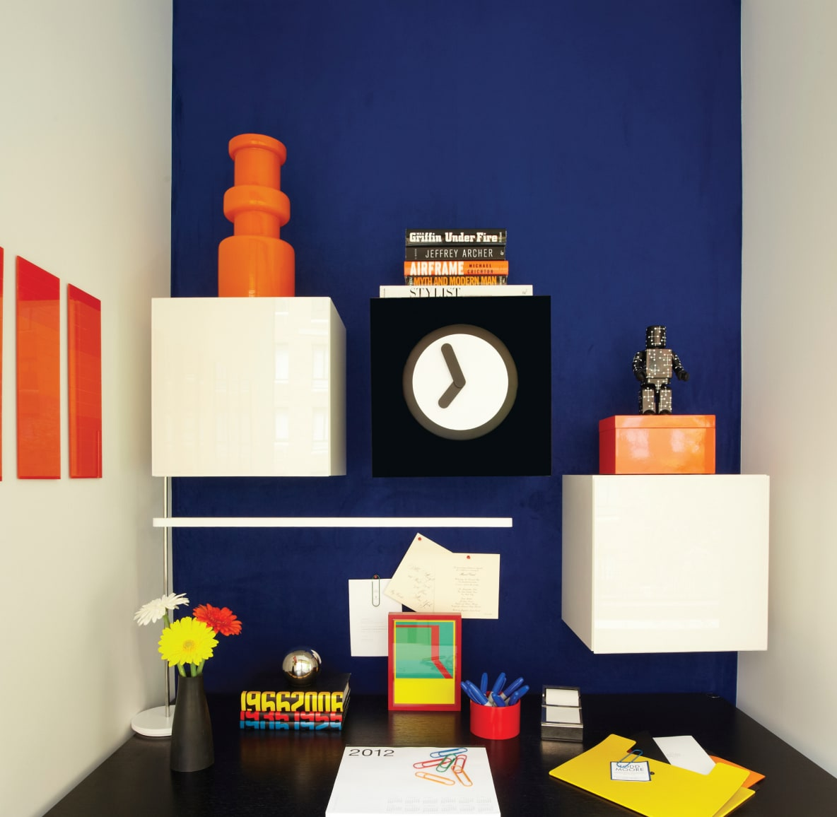 Colorful desk station with bright blue accent wall, bright flowers and bold knick-knacks
