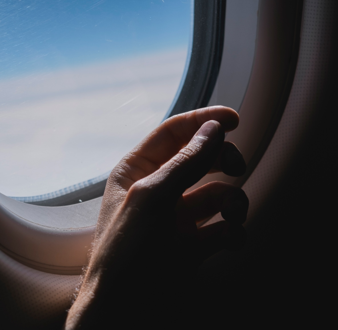 A hand in the shadow of an airplane window, clouds and blue sky in the background