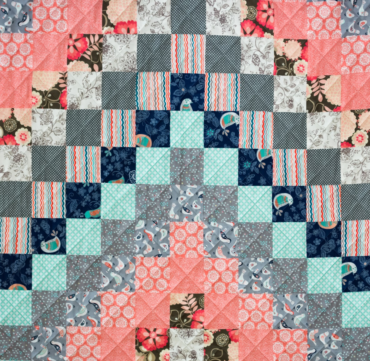 A handmade quilt with blue, pink and white patterned squares
