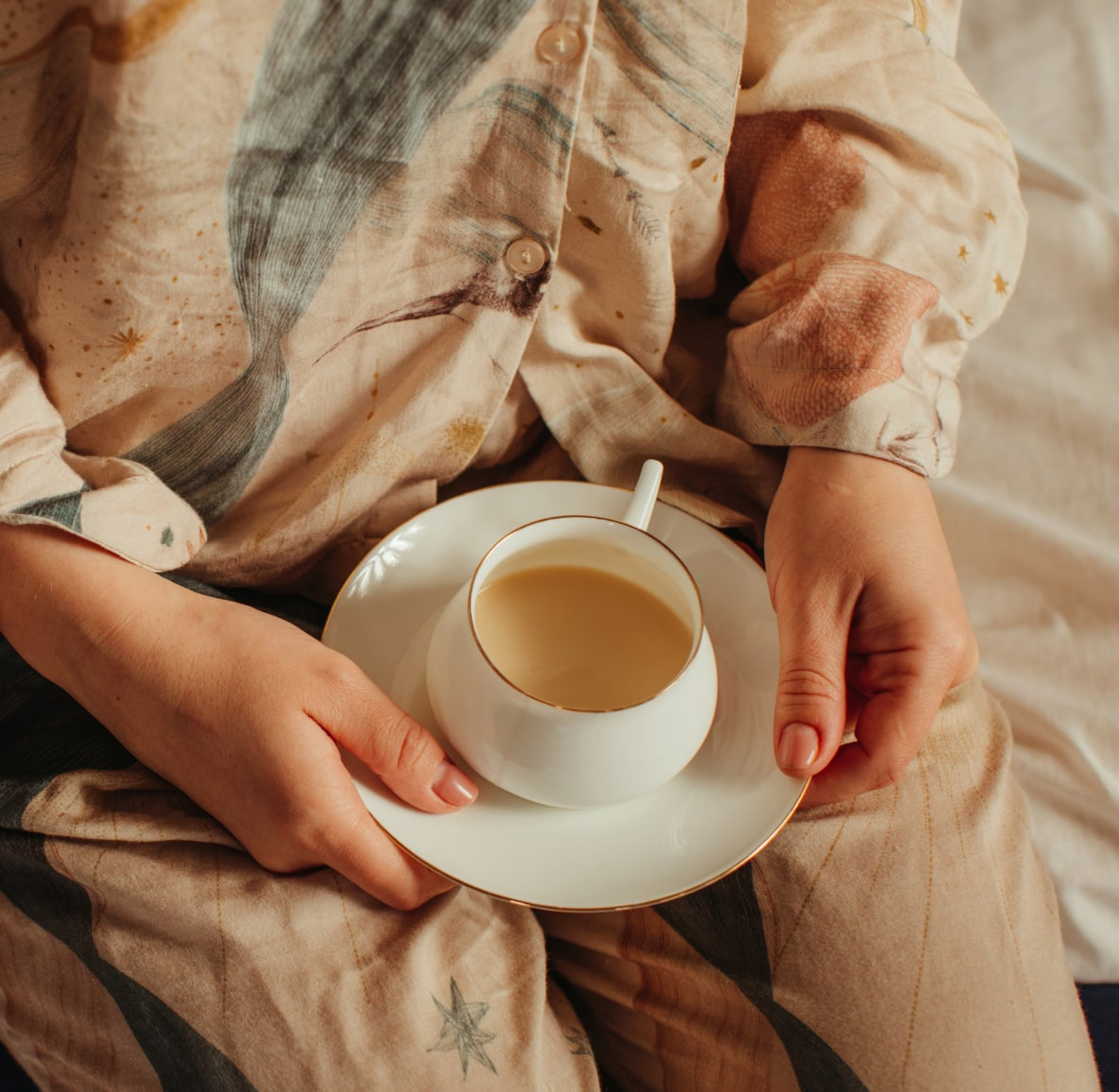 Woman in loose pajamas sitting on the edge of a bed with a cup of tea