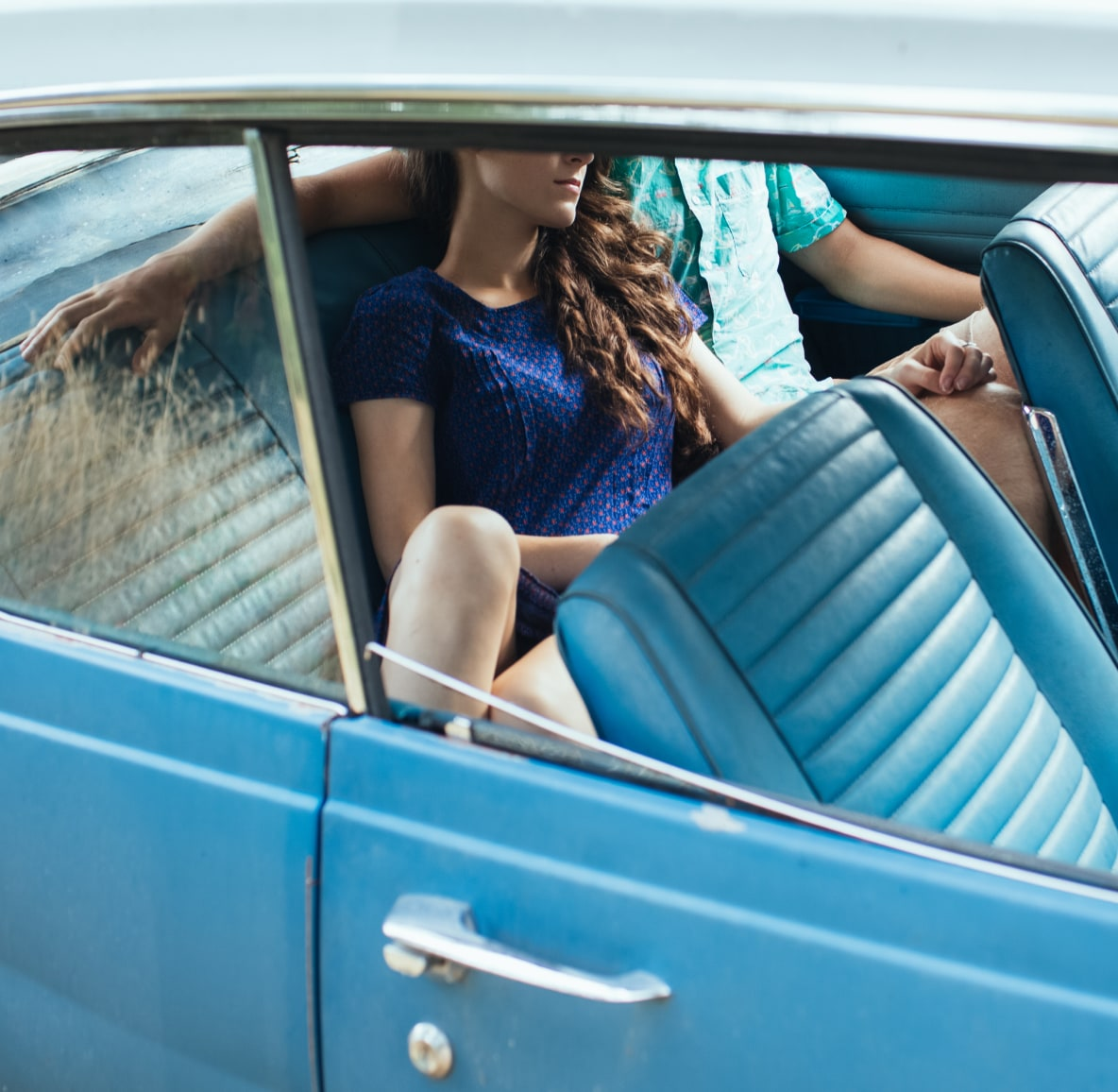 Man and woman couple sitting in the back seat of a vintage car on a date