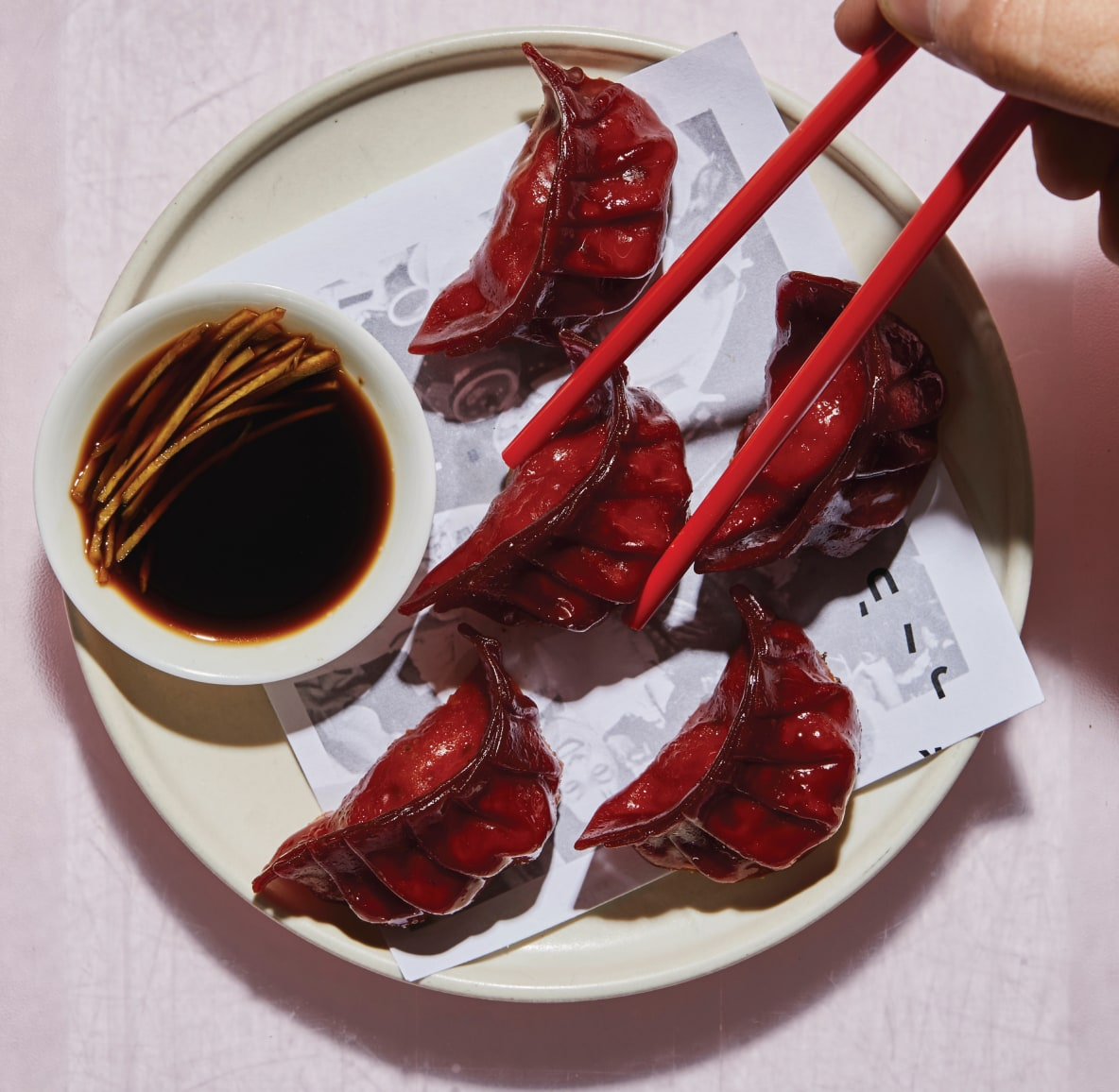 A plate of artisanal red potstickers with a side dipping sauce