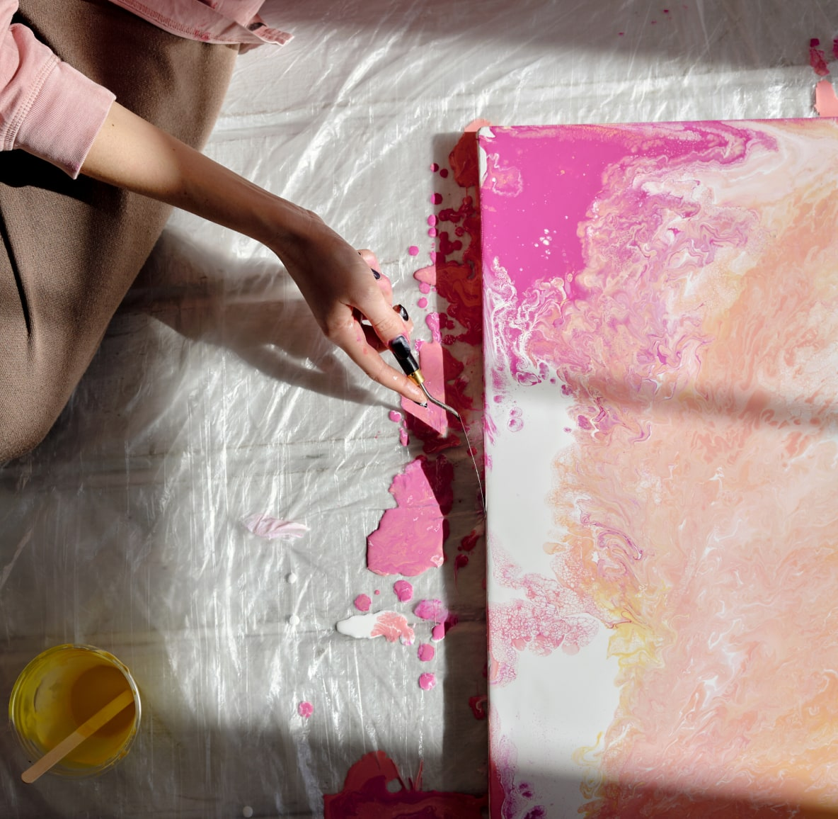 Woman's hand painting a canvas with pink and peach paint.