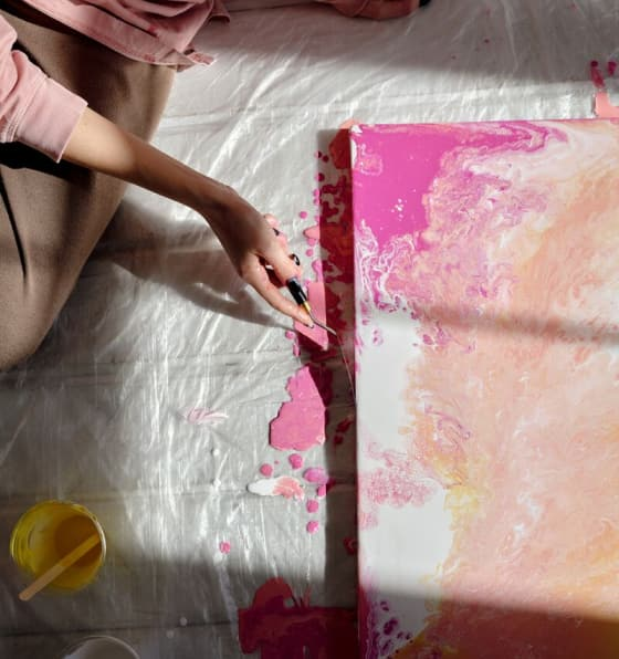 A painter touches up the edge of a canvas showing various shades of pink on white