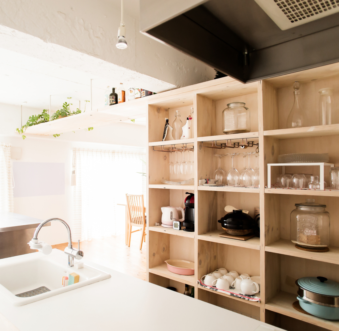 A wall of wood shelves in a brightly lit kitchen