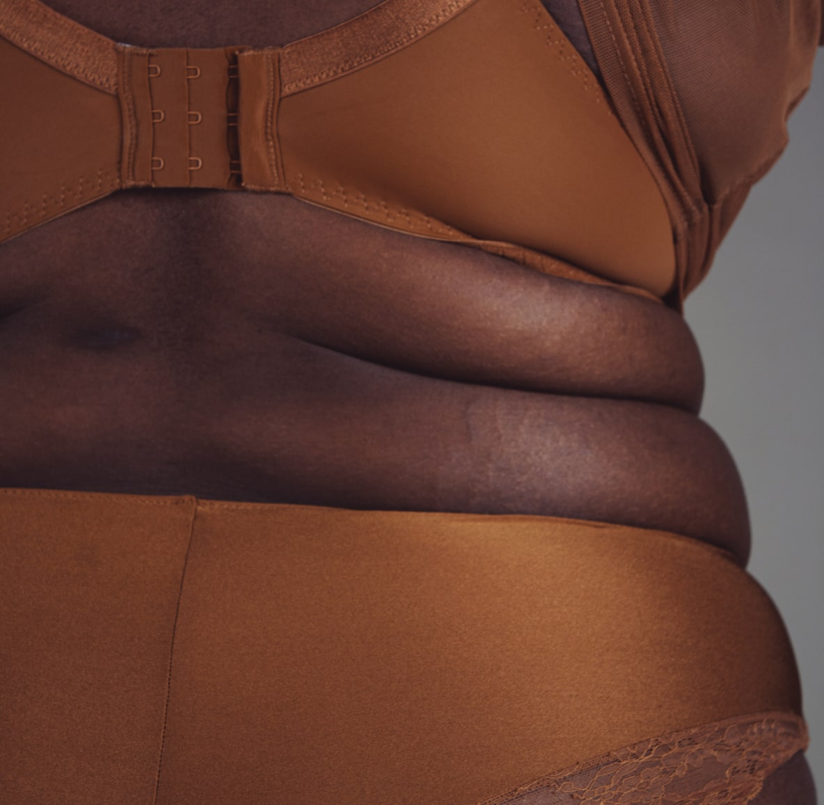 Hips and waist of a plus-size woman wearing nude-colored bra and underwear