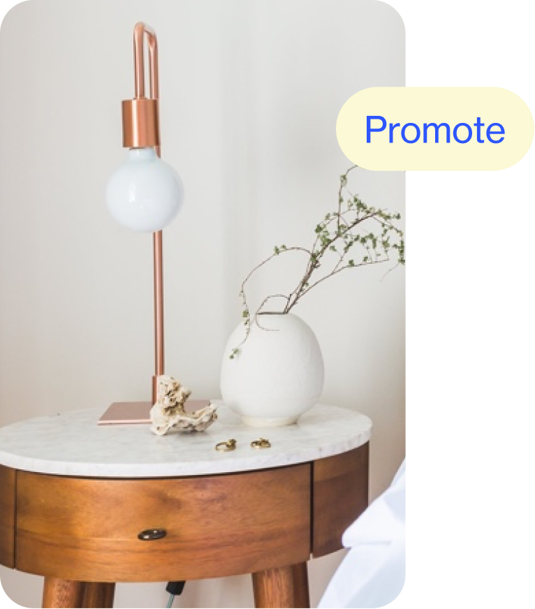 Circular wooden side table with white marble top, featuring a small white vase and simple bulb lamp