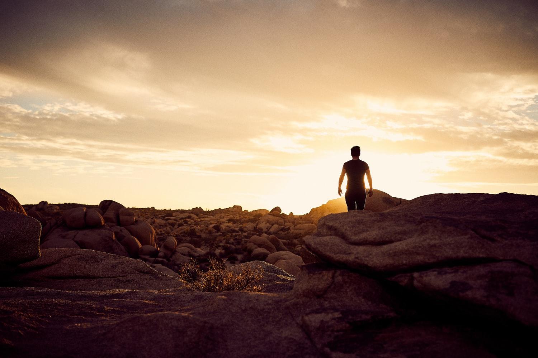 A man walking towards sun