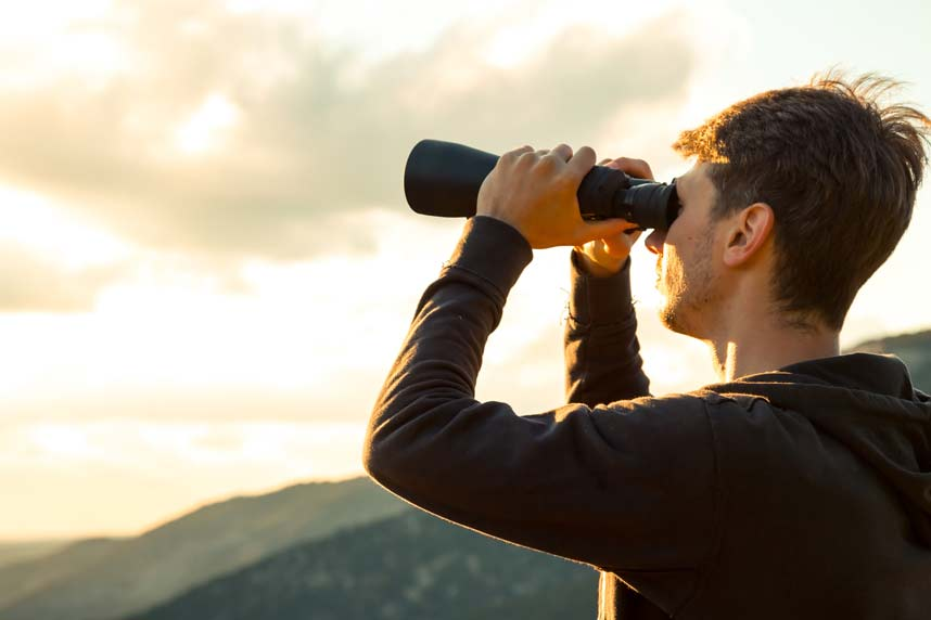 Man holding a telescope looking at the view.