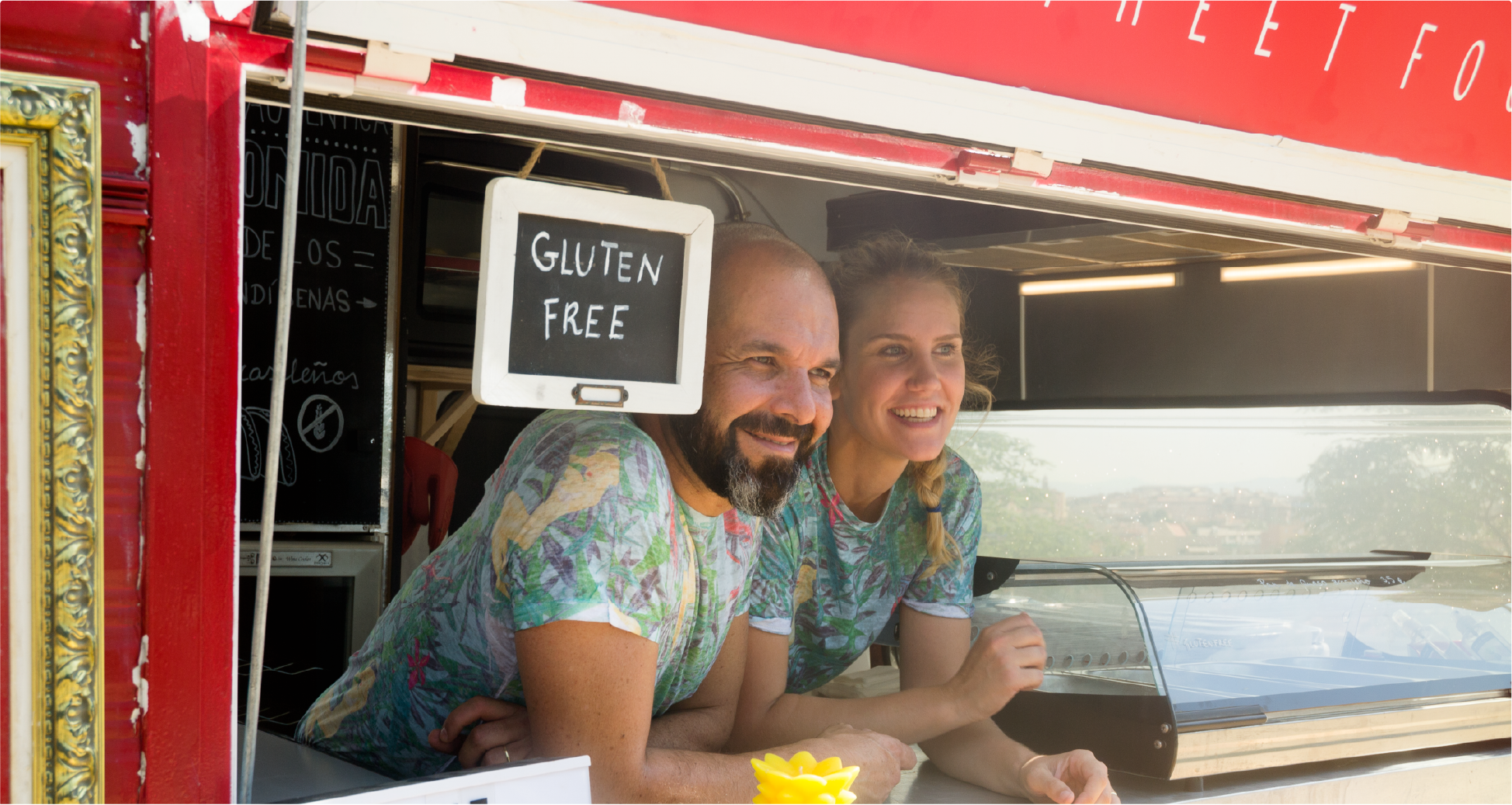 Male and female smiling inside the windows of a food truck.