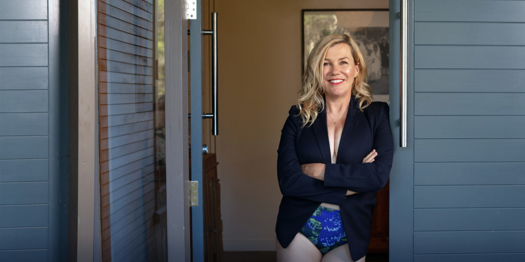 Image of Robyn Melcomm in a blazer and Undies, standing in a doorway to her home.