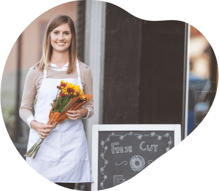 A lady standing outside of her florist storefront, smiling while holding a beautiful arrangement of flowers.