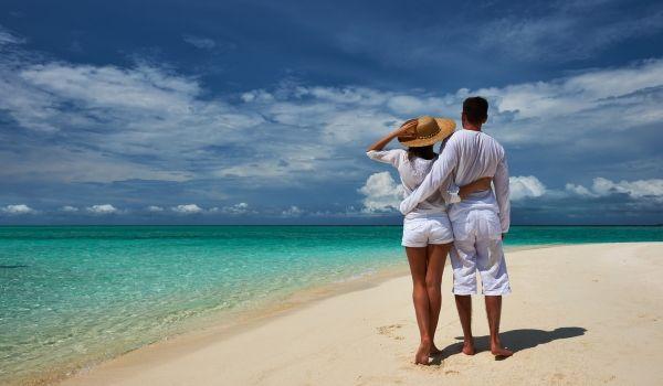 Couple walking on a white-sand beach