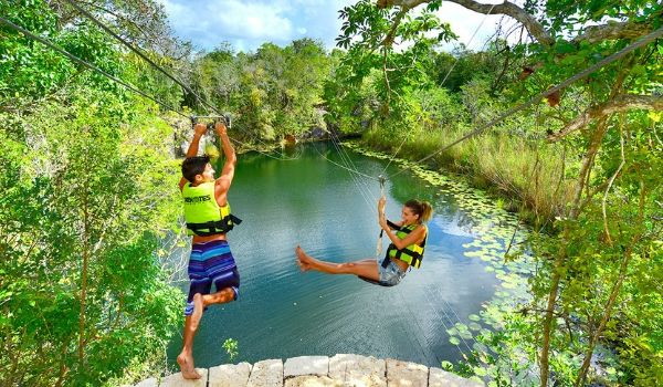 Young boy and girl ziplining over lagoon