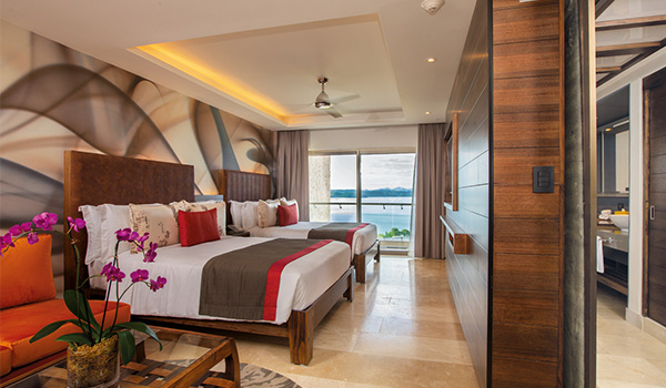 Resort suite with two beds and a view of the ocean from the balcony