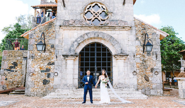 Bride and groom posing in front of an old church