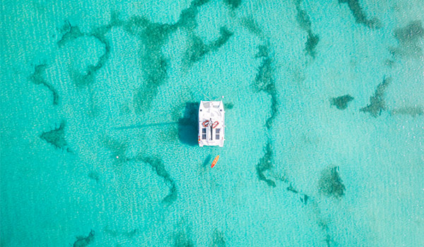 Aerial view of a catamaran in the middle of a coral reef