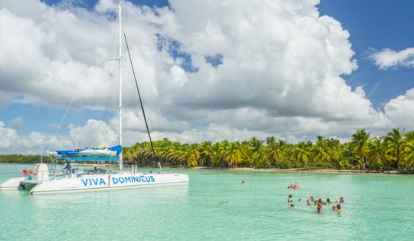 Groupe de vacanciers nageant le long d'un catamaran