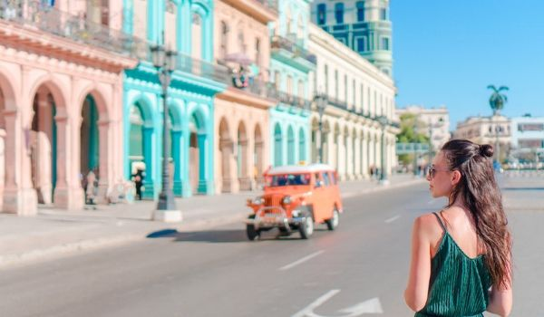 Woman walking by colourful buildings in Havana
