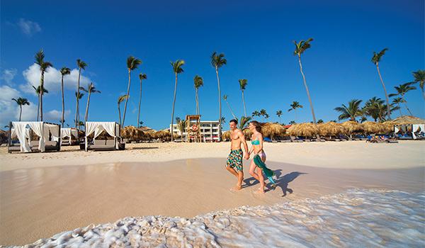 Homme et femme marchant sur la plage main dans la main